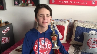 Chase sitting in his room with a basketball trophy