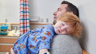 Child asleep on fathers shoulder in exam room