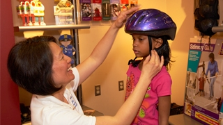 child trying on biking helmet