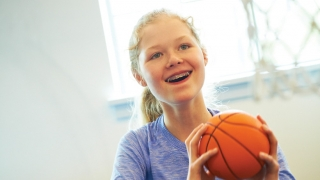 young girl holding basketball