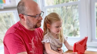 Father and daughter sharing tablet screen