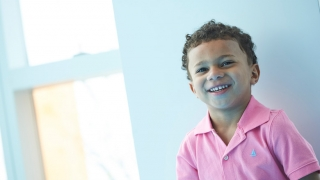 Cruz smiling wearing in a pink shirt