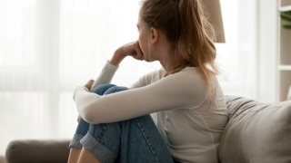 young depressed teen siting in couch looking out window