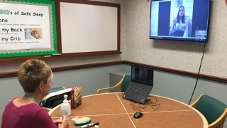 Nurse and family engaged in tele-education session