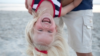 girl on beach hanging upside down smiling
