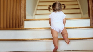 Infant girl climbing staircase