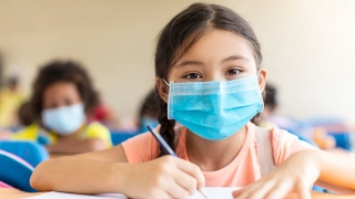 Children in classroom wearing protective masks