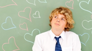 Boy standing in front of hearts drawn on chalkboard