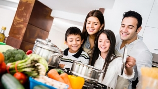 Family in kitchen watching over stove