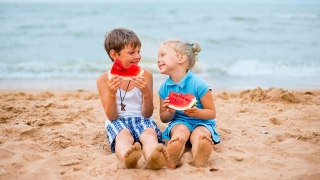 Two kids on the beach eating watermelon