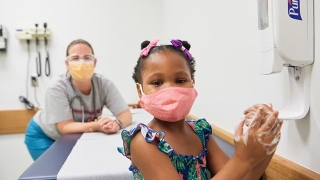 Young girl wearing mask in doctor's office with nurse