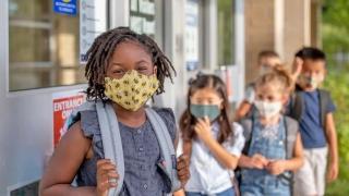 Children gathering outside of school wearing masks