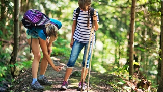 Mother spraying daughter's leg with bug repellent