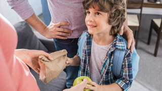 Boy receiving lunch and an apple from parent