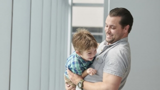 Father holding rowdy child