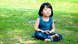 Young girl sitting in the grass, practicing breathing