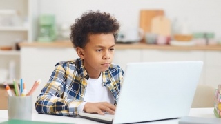 Young boy looking at laptop screen