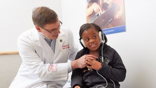Doctor giving hearing exam to female patient