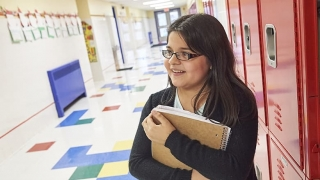 Adolescent girl holding books in school hallway
