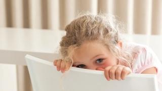 Shy girl hiding her face behind a chair