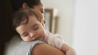 Mother holding sleeping infant