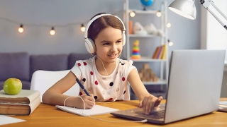 Young girl attending online school course