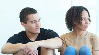 Teenaged boy and girl sitting together