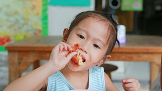 Young girl eating shrimp