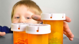 young boy reaching for pill bottles