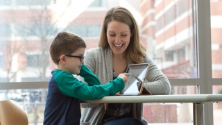 Therapist working with child smiling playing with computer