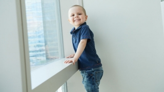 Young boy cancer patient in hospital window smiling