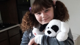 Young girl hospital patient smiling holding stuffed animal