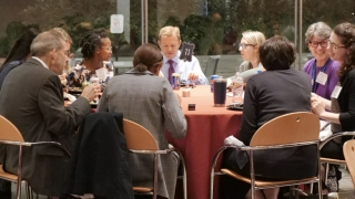 Medical professionals sitting around table having dinner at conference