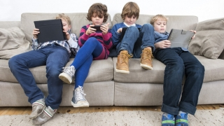 Kids on couch playing with gadgets being inactive