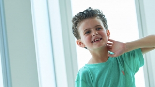 Young boy cancer patient sitting by window smiling