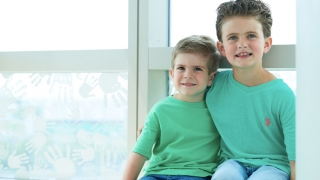 Young cancer patient sitting with brother in window smiling