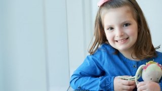 Young girl cancer patient smiling with stuffed animal