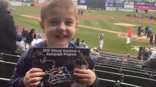 Cardiac patient at baseball game holding up program