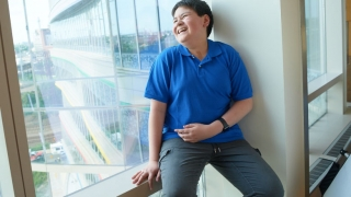 Young boy cancer patient sitting in hospital window laughing