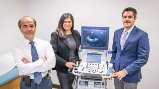 Three doctors standing with ultrasound machine