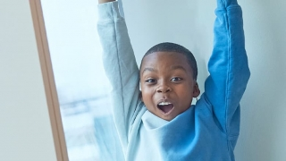 Young boy with arms up in celebration