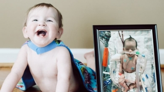 Jaxon smiling next to photo of him in hospital as infant