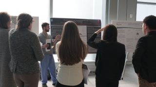 Conference attendees listening to a poster presentation