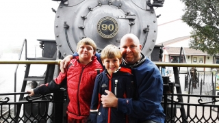 Sam standing outside with his brother and father by a locomotive