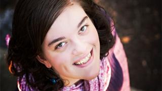 Sara smiling looking up at the camera outside