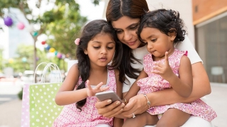 Mom with two daughters shopping on smart phone