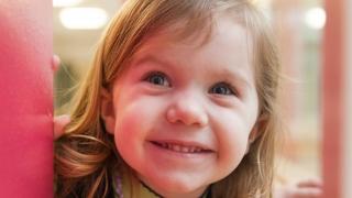 smiling child peeking around corner