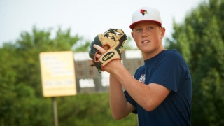 Teenage boy in baseball field holding ball and glove