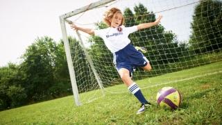Tween girl playing soccer in front of net