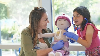 Child Life worker playing dolls with oncology patient